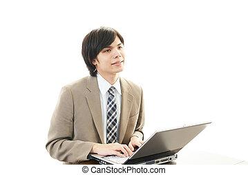 Smiling businessman using laptop