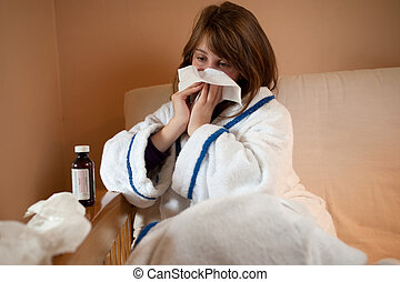 Girl blowing her nose - Teenage girl with a cold blowing her...