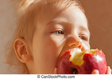 Child girl eating big red apple