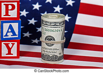 The American Way - Toy blocks and wad of cash on flag