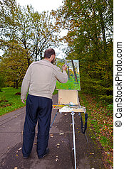 artist with easel painting en plein air landscape painting...