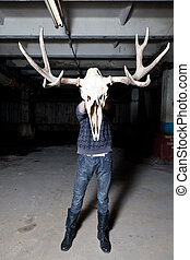 Man with deer skull in the basement