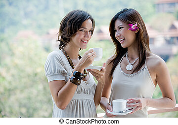 Friends Having Coffee - Two young women together outside...
