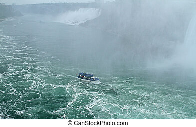 Nagara Falls, Ontario, Canada - Tourists ride a boat to...