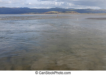 Tidal currents - A stretch of water, a tidal estuary, with a...
