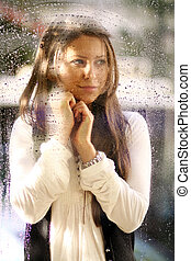 Young woman near the window after the rain - Portrait of a...