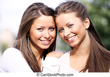 Two sisters young women - Two young twins girls in the...