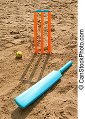 Toy cricket set on beach - Bright orange toy cricket set on...