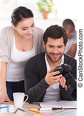 Good shots! Two co-workers discussing something while man holding camera and smiling with people working on background