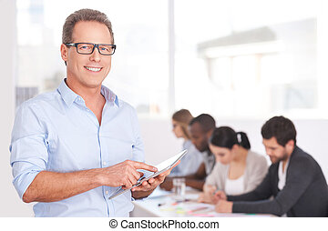 Confident team leader. Confident young man in glasses working on digital tablet and smiling while people working on background
