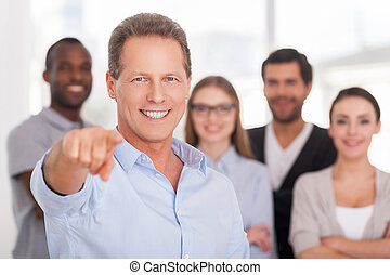 I choose you! Confident mature man pointing you and smiling while group of people in casual wear standing on background