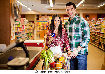 Using a credit card at the store - Cute happy couple paying...