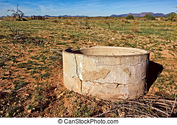 Waterless - An old cracking cement water trough at an...