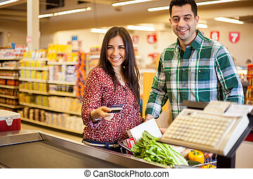 Buying groceries with a credit card - Beautiful young woman...
