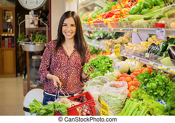 Buying healthy food at the store - Happy young brunette...