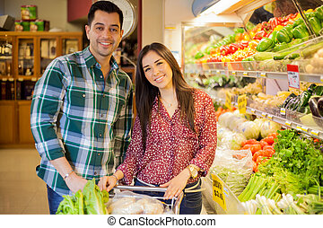 Cute couple in a grocery store - Happy Hispanic newlyweds...