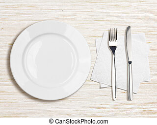 white plate, knife, fork and napkin top view on wooden table