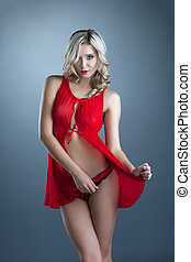 Portrait of charming blonde posing in red negligee, close-up
