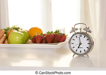 alarm clock with tray of fresh fruit, strawberry, apple and...