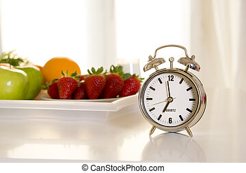 alarm clock with tray of fresh fruit, strawberry, apple and orange in the background