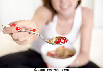 close up of spoon of woman eating cereal with strawberries -...