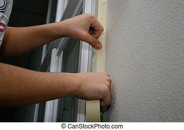 Person auf Baustelle - Person klebt Abdeckband an...