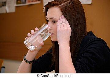 Jugendliche hat Kopfweh und trinkt Wasser - Teenager mit...