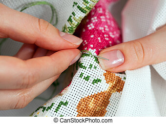 Fine needlework - Fingers of young women, cross embroidery.
