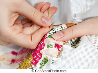 Embroidery - Woman hands doing cross-stitch. A close up of...