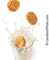 Three cookies biscuits falling into a glass mug full of...