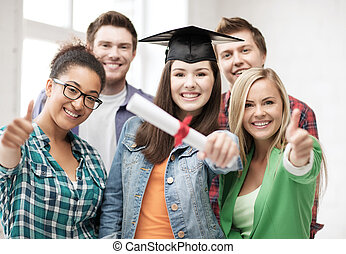girl in graduation cap with diploma and students - education...