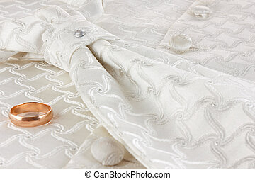 Golden ring and cravat on fabric background
