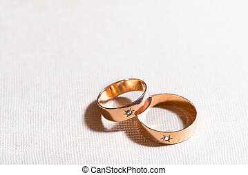 Weding Rings - two golden wedding rings on the tablecloth
