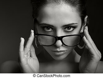 Sexy woman in modern glasses looking serious. Black and...