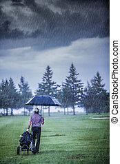 Golfer on a Rainy Day Leaving the Golf Course (the game is...