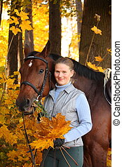 Beautiful blonde woman and brown horse in autumn
