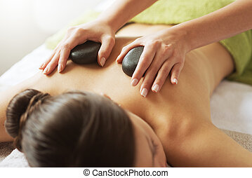 Hot stone therapy - Young woman receiving a hot stone...