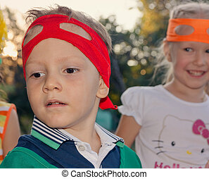 Handsome young boy at a childs birthday party wearing a...