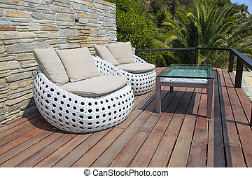 White outdoor furniture on wood resort terrace - White...