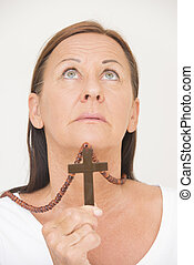 Praying woman with christian crucifix