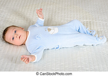 Cute baby boy is lying on the gray carpet looking at camera