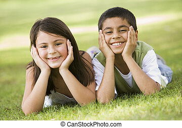 Two children relaxing in park looking to camera