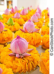 Row of lotus and yellow flower garlands on tray with...