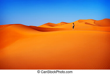 Woman traveler in desert - Woman walking in desert, active...