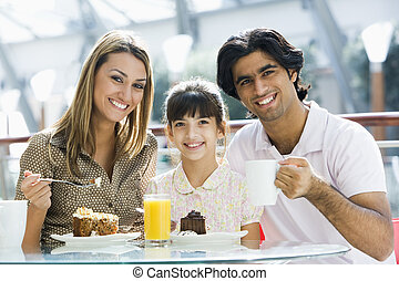 Family having snack at cafe looking to cafe