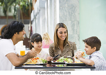Family enjoying lunch at cafe - Family enjoying meal sitting...