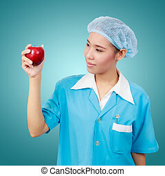 Female dentist holding an apple and  metal medical equipment tools for teeth dental care