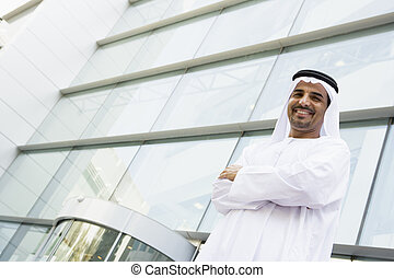 A Middle Eastern businessman standing outside an office block