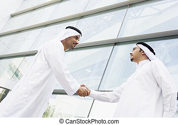 Two Middle Eastern businessmen shaking hands outside an...