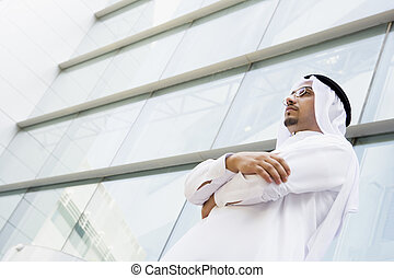 A Middle Eastern businessman standing outside an office...